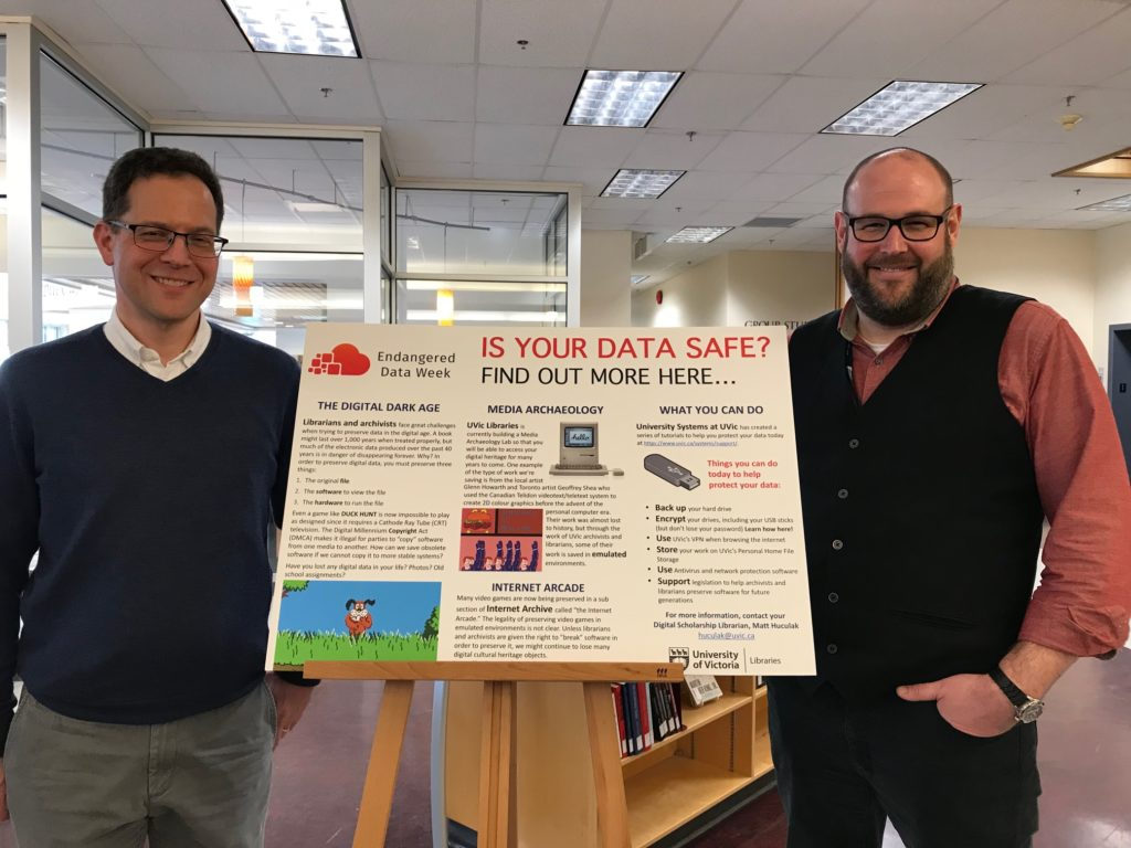 """Figure 1: John Durno and Matt Huculak in front of the """"Is Your Data Safe"""" poster"""